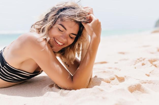 Spectaculaire europese vrouw liggend op zand met gesloten ogen. geweldig vrouwelijk model in zwarte bikini chillen in het resort.
