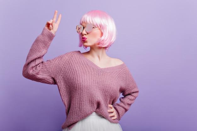 Spectaculaire jonge blanke meisje poseren met kussende gezichtsuitdrukking geïsoleerd op paarse muur. binnenfoto van charmante europese vrouw in trendy periwig die voor de gek houdt.