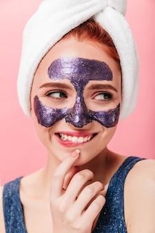Spectaculaire jonge vrouw die kuur met oprechte glimlach doet. studio die van blij meisje met gezichtsmasker en handdoek is ontsproten.