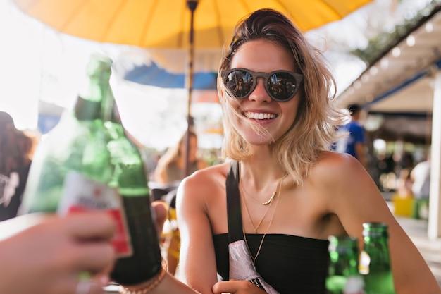 Spectaculaire jonge vrouw iets vieren in zomerterras. buiten foto van vrij blond meisje bier drinken met vrienden in warme dag.