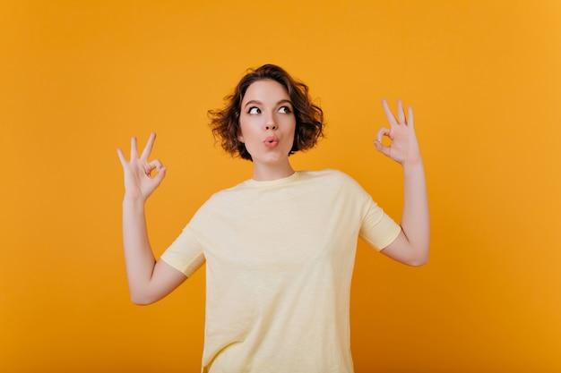 Spectaculaire jonge vrouw met grappige tatoeage dansen op lichte muur. kortharig onbezorgd meisje draagt een geel t-shirt.
