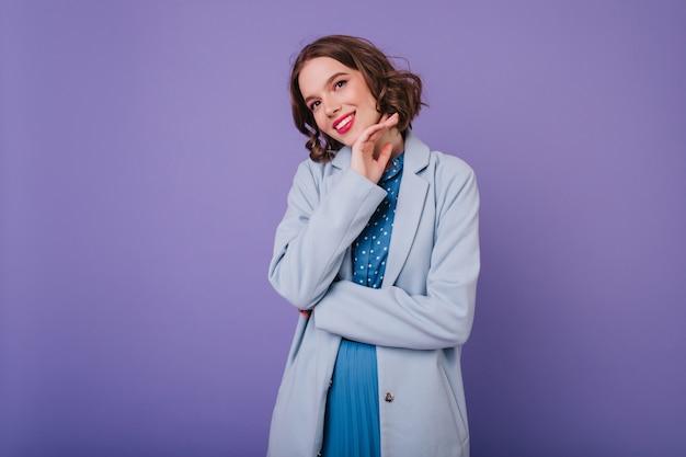 Spectaculaire jonge vrouw met krullend kapsel lachen op paarse muur. prachtig vrouwelijk model in blauwe jas genieten van fotoshoot.