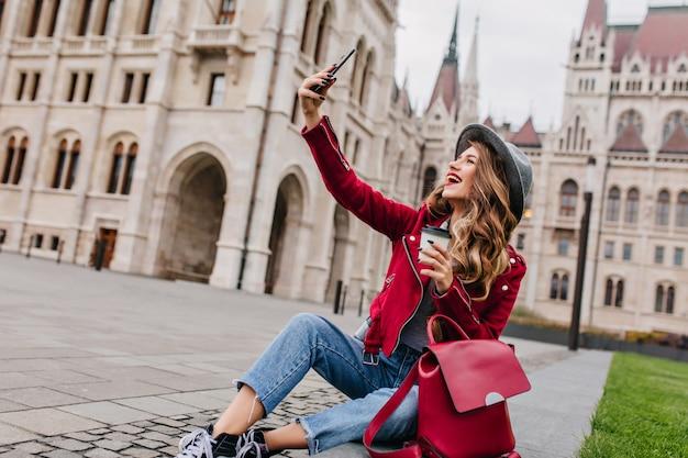 Spectaculaire jonge vrouw zittend op de grond met rugzak en het nemen van foto van zichzelf