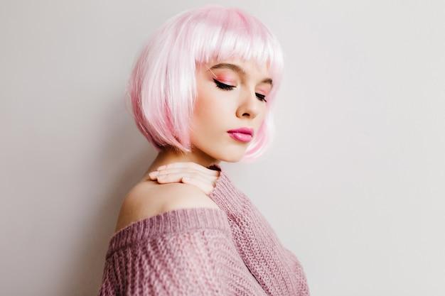 Spectaculaire jongedame in stijlvolle periwig met gesloten ogen. vrij wit meisje draagt roze pruik poseren in zachte paarse trui.