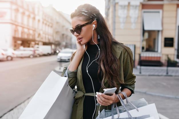 Spectaculaire latijns-vrouw in stijlvolle zonnebril chillen in de stad en muziek luisteren in oortelefoons