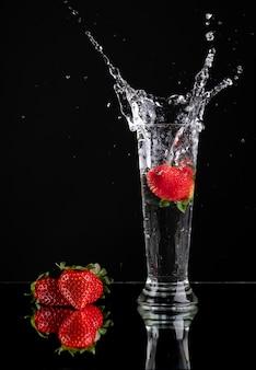 Spectaculaire plons van een aardbei in een glas met daarna drie aardbeien
