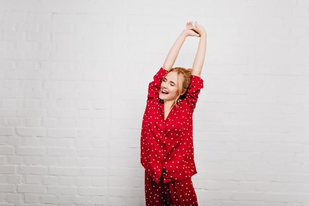 Spectaculaire vrouw in trendy nachtkleding die zich uitstrekt met een glimlach. enthousiast meisje dat van goedemorgen geniet en op witte muur stelt.