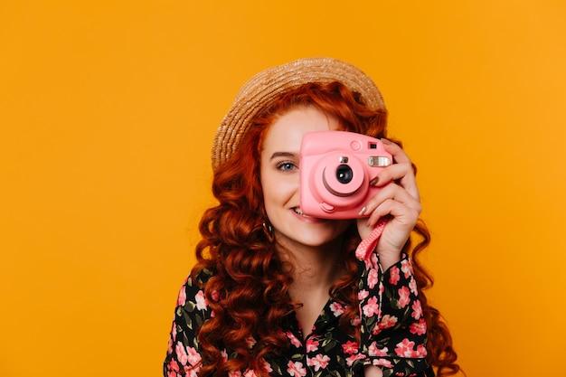Spectaculaire vrouw met golvend rood haar en blauwe ogen bedekt haar gezicht en maakt foto's met een minicamera.