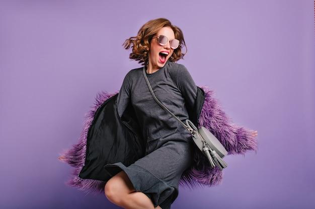 Spectaculaire vrouw met opgewonden gezichtsuitdrukking die op paarse achtergrond springt en zingt