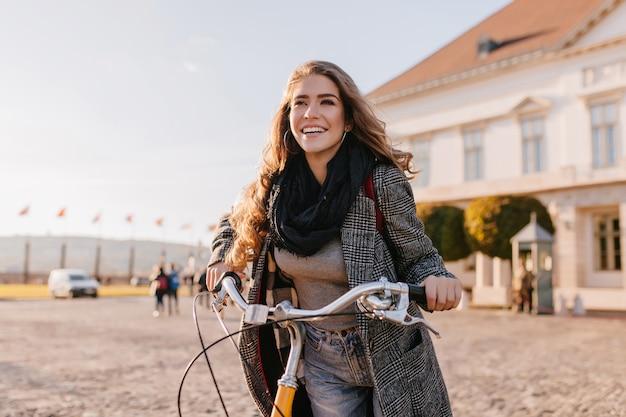 Spectaculaire vrouw met zwarte sjaal poseren met blij gezicht expressie in de buurt van groot huis