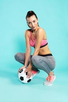 Speel met mij jonge en sportieve mooie vrouw in sportkleding zittend op hunkers met voetbal