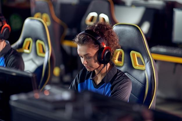Speel om gefocuste tiener gemengd ras meisje professionele vrouwelijke gamer te winnen met een koptelefoon aan het spelen