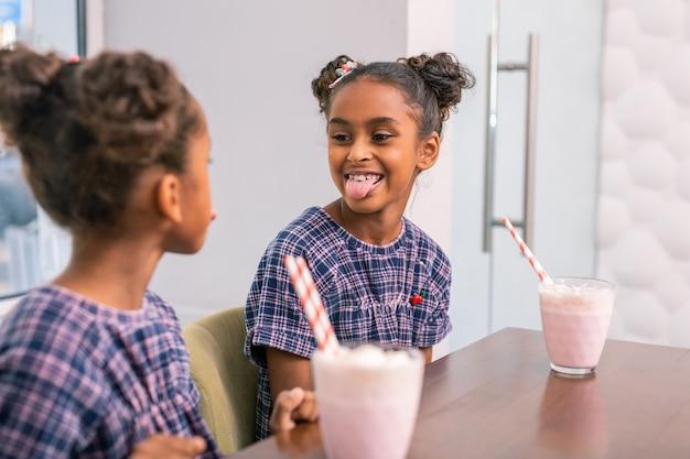 Speel trucs. grappig donkerharige meisje met mooi kapsel tong tonen tijdens het spelen van trucs met broer of zus