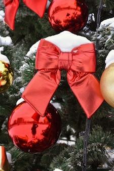 Speelgoed aan de kerstboom, een rode strik aan de boom in de sneeuw