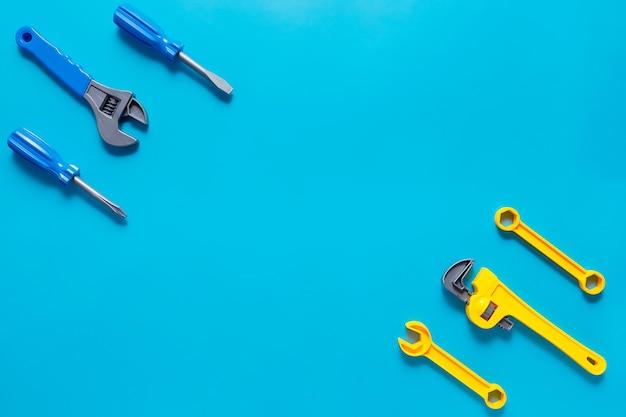 Speelgoed achtergrond. bovenaanzicht van speelgoedgereedschap op blauwe achtergrond met kopie ruimte voor tekst.