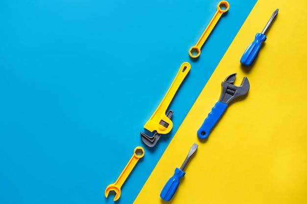 Speelgoed achtergrond. bovenaanzicht van speelgoedgereedschap op blauwe gele achtergrond met kopie ruimte voor tekst.