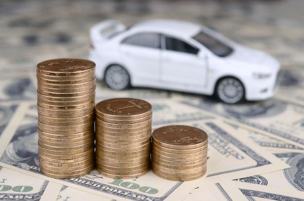 Speelgoed automodel op de stapels van gouden munten ligt op veel dollarbiljetten