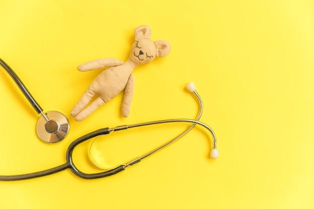 Speelgoed beer en geneeskunde apparatuur stethoscoop geïsoleerd op gele achtergrond