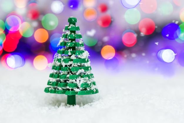Speelgoed boom bestrooid met sneeuw staat in de sneeuw op de achtergrond van een prachtige kleurrijke