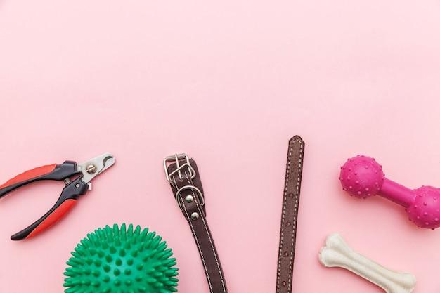 Speelgoed en accessoires voor spelen en trainen van de hond geïsoleerd op roze tafel