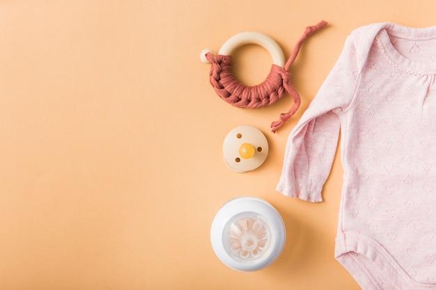 Speelgoed; fopspeen; melkfles en roze baby onesie over een oranje achtergrond
