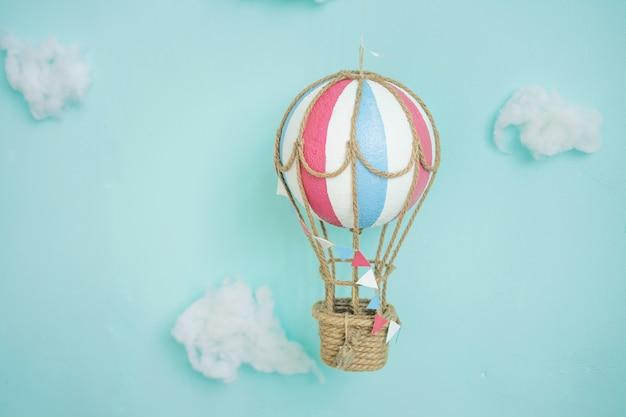 Speelgoed hete lucht ballonnen en wolken op een blauwe muur