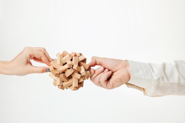 Speelgoed houten puzzel in handen op wit wordt geïsoleerd