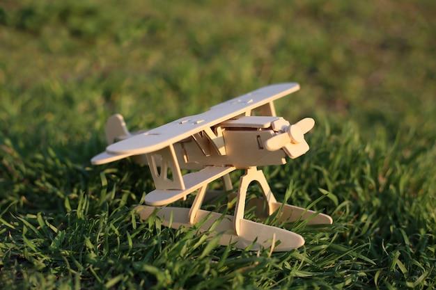 Speelgoed houten vliegtuig staat op het groene gras