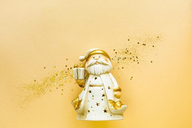 Speelgoed kerstman met een geschenkdoos met gouden kleur op een gele achtergrond vakantieconcept, plat leggen, bovenaanzicht, kopie ruimte