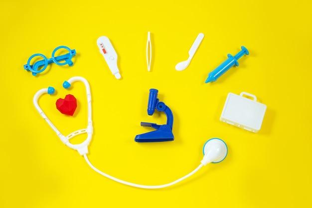 Speelgoed medische hulpmiddelen op een gele achtergrond.