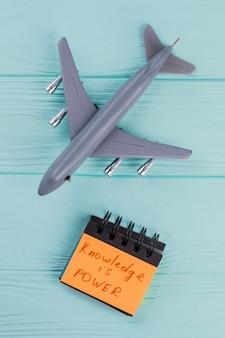 Speelgoed modelvliegtuig en gele sticker geïsoleerd op turkooizen achtergrond. kennis is macht op sticker.