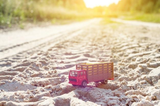 Speelgoed retro vrachtwagen op de weg - symbool van vrachtvervoer