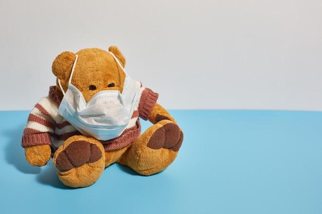 Speelgoed teddybeer in een beschermend medisch masker. bescherming tegen coronavirus en ziektekiemen.