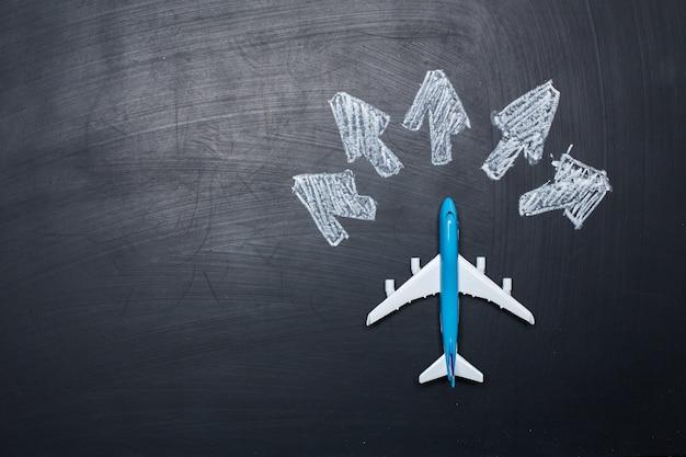 Speelgoed vliegtuig over schoolbord achtergrond en pijlen tekeningen