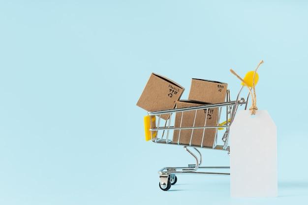 Speelgoed winkelwagentje met dozen en lege tag op blauwe achtergrond. kopieer ruimte voor tekst of ontwerp. uitverkoop