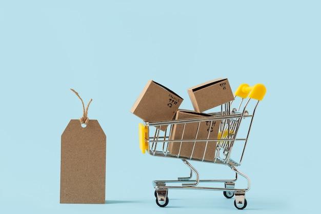 Speelgoed winkelwagentje met dozen en lege tag op blauwe achtergrond