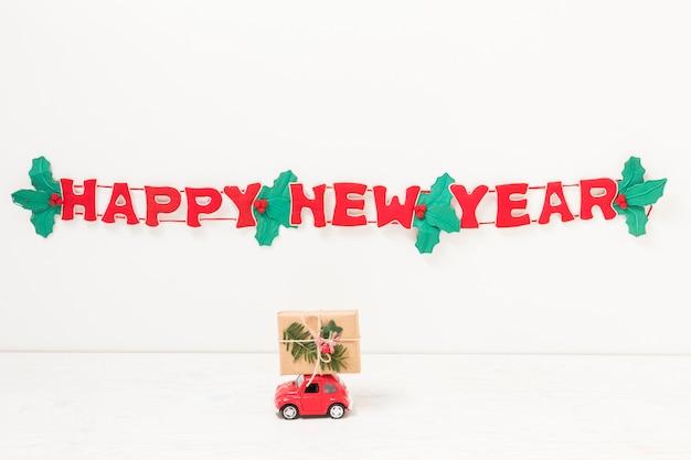 Speelgoedauto met cadeau in de buurt van gelukkig nieuwjaar inscriptie