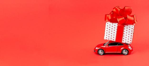 Speelgoedauto met cadeau op een rode muur