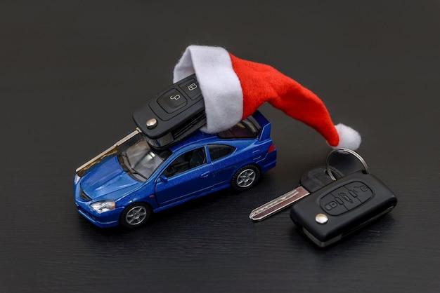 Speelgoedauto met kerstmuts en sleutel op zwart