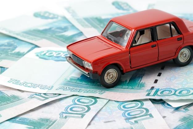 Speelgoedauto op de achtergrond van bankbiljetten.