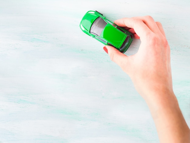 Speelgoedauto vrouw hand. aankoop verzekering lening reizen concept