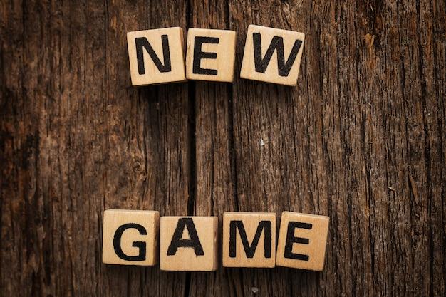 Speelgoedbakstenen op tafel met woord nieuw spel