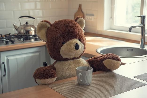 Speelgoedbeer zit aan een tafel in een lichte, moderne keuken met een glas thee
