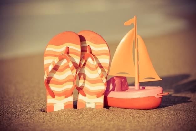 Speelgoedboot en slippers op het strand