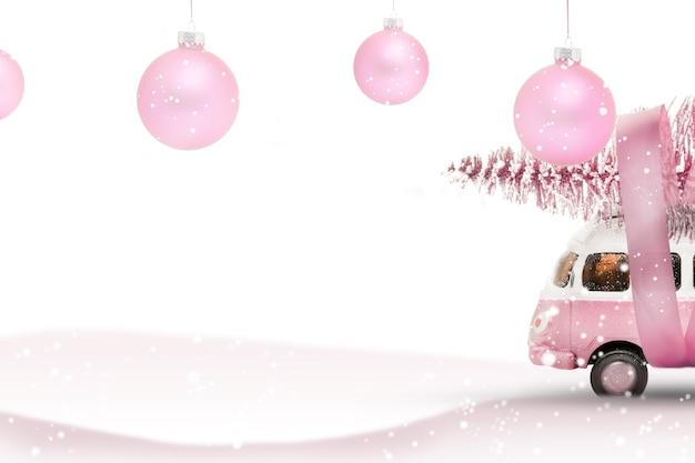 Speelgoedbus auto draagt een kerstboom uit het bos. roze en witte kleuren, wintervakantie nieuwe jaarsfeer.