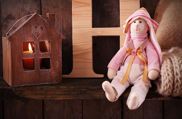 Speelgoedkonijntje met brief, wollen sjaal en huis op houten tafel