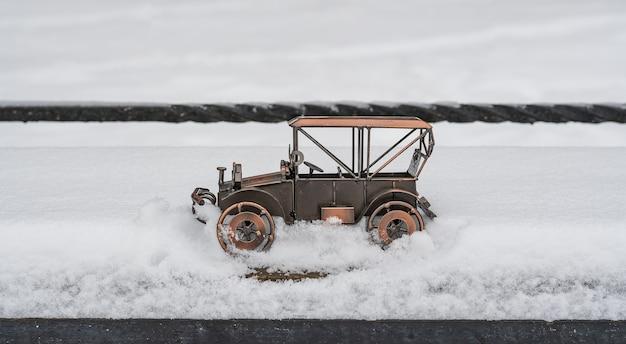 Speelgoedmodel van een retro-auto die diep in de sneeuw vastzit op een parkstraat