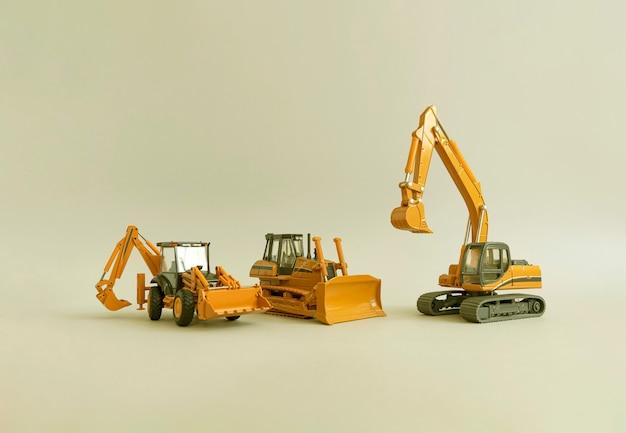 Speelgoedmodellen frontale graaflaadmachine mijnbouw graafmachine en bulldozer bouwmachines grijze achtergrond