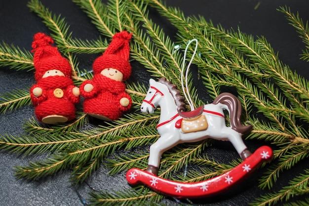 Speelgoedpaard en twee speelgoedkinderen op kerstboomtak