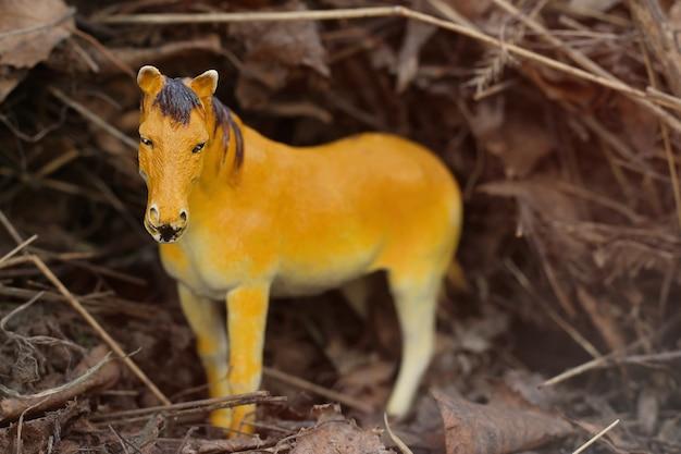 Speelgoedpaard in de natuur gefotografeerd als echt tussen het droge gras als hooibergen